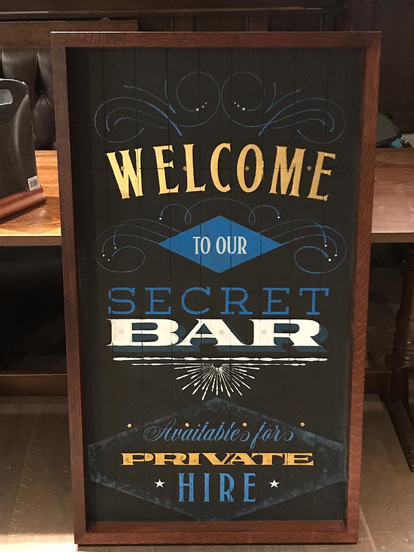 Hand painted welcome sign for entrance to bar