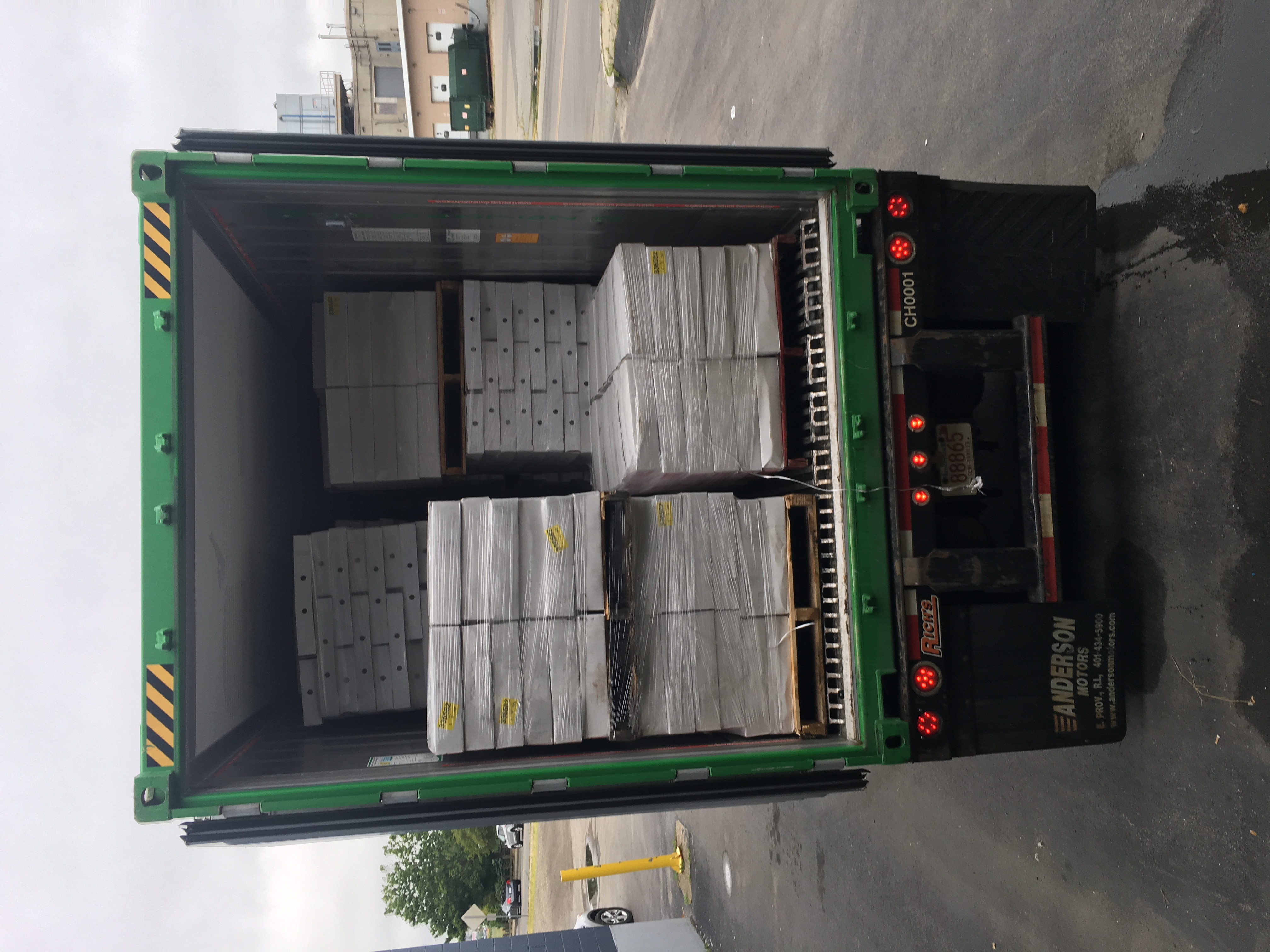 A delivery truck being loaded with pallets of fish.