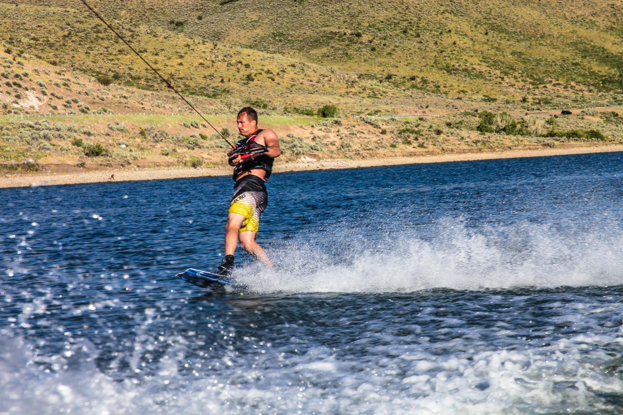 Hard out on the wakeboard's tow edge behind our motor boat