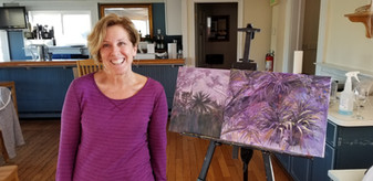 Beginner painter, Judy Switick, next to her new tropical oasis painting.