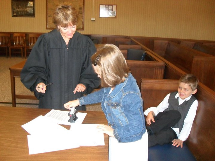 #Bob looks on as #Cindy stamps her adoption paperwork with the judge.