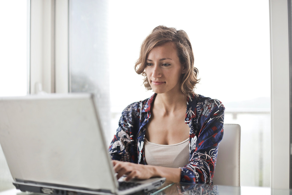 Woman sitting on a desk with her computer at home planning her week