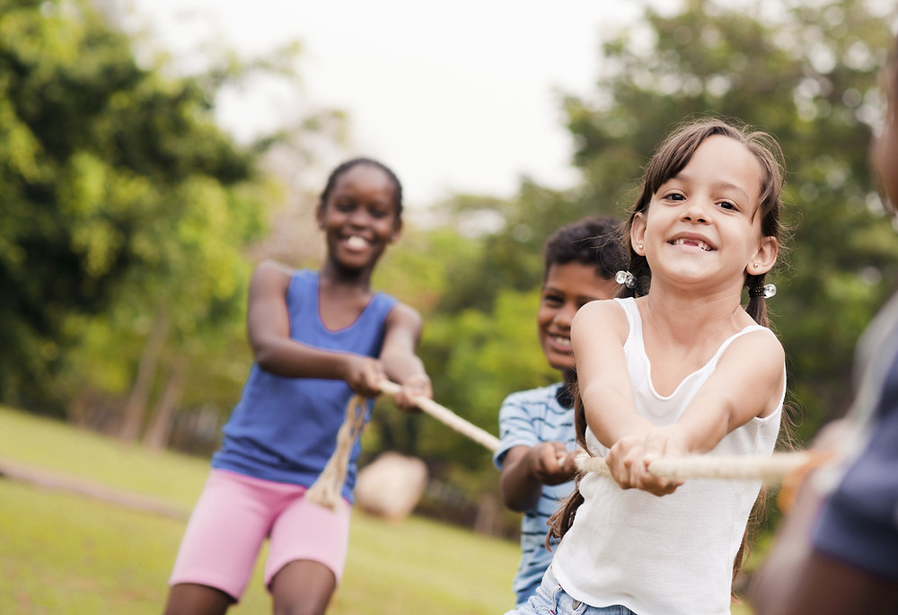 Happy kids playing on the park during a summer camp