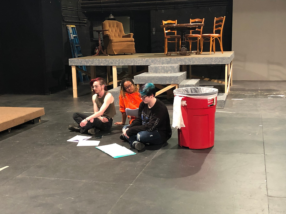 Image of a rehearsal space with three actors, seated.
