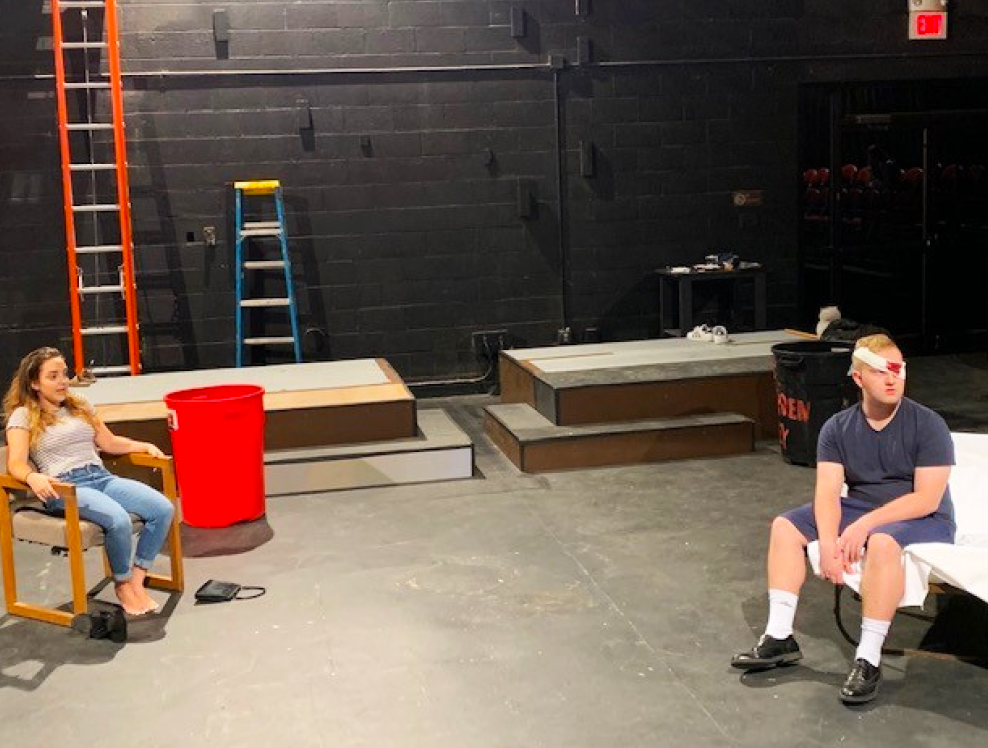 Two actors sitting in a rehearsal space