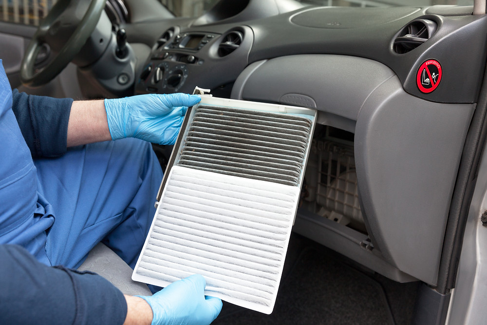 A dirty cabin air filter next to a clean cabin air filter