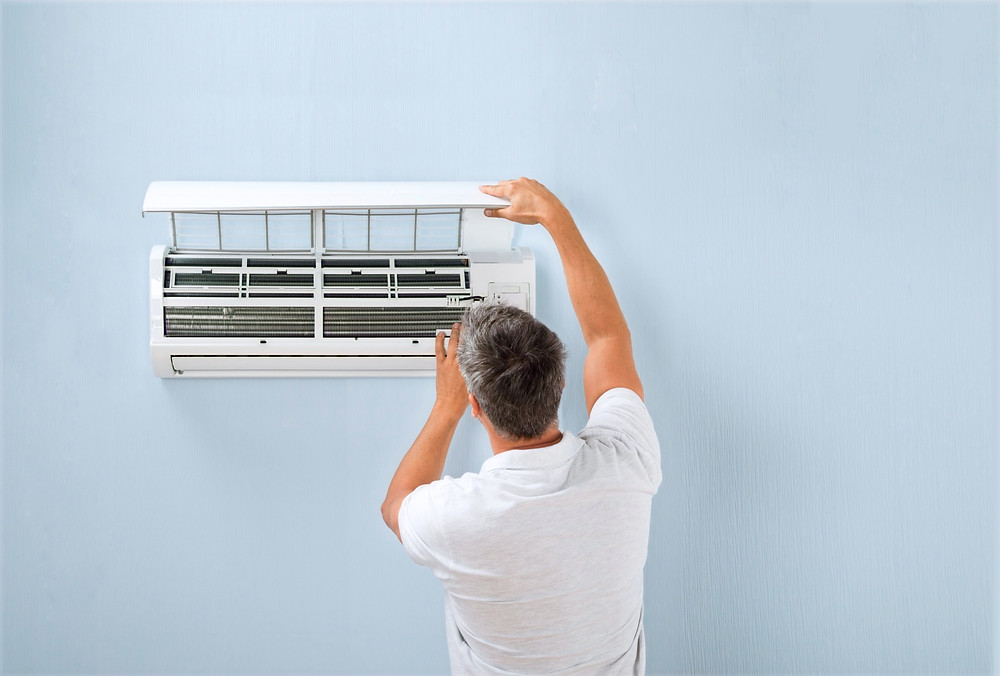 An older man or dad checking am air conditioning unit
