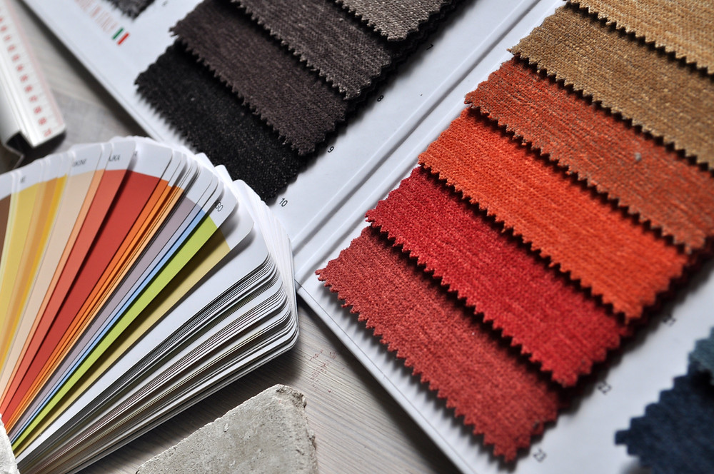 Paint and fabric samples in rust, orange, yellow, and gray