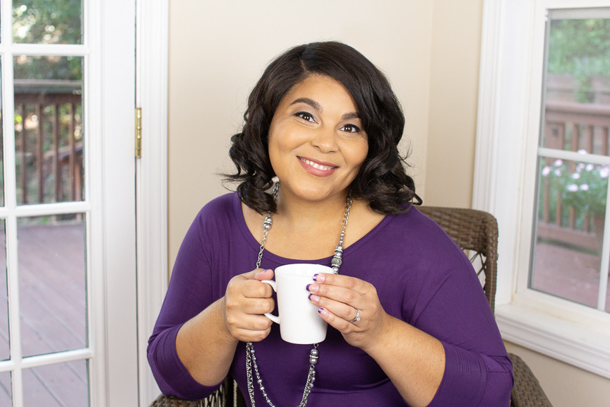 African American woman wearing purple and holding a cup of coffee