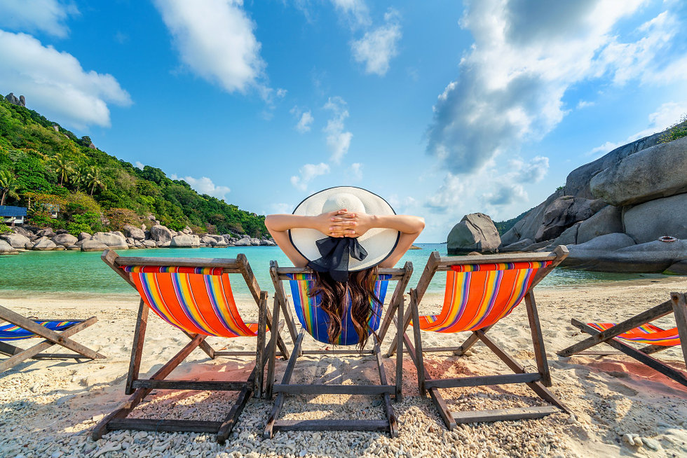 woman-with-hat-sitting-on-chairs-beach-i