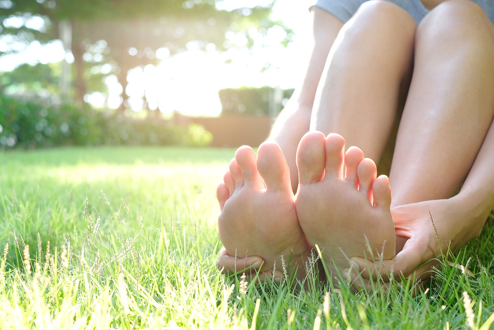 Foot pain .Woman sitting on grass Her ha