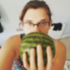 A picture of Vikki holding a small watermelon up to her face.