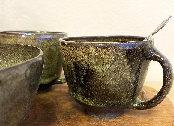 Grön kopp i svart lera