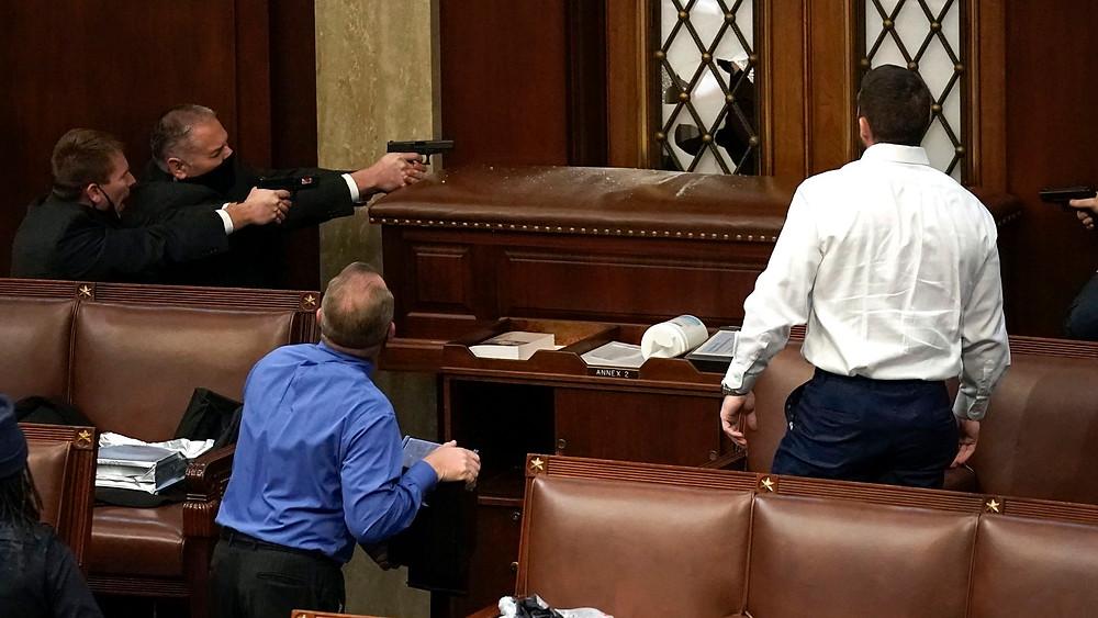 Des agents de sécurité du Capitol pointent leur arme contre un manifestant dans l'enceinte du Capitol - 6 Janvier 2021