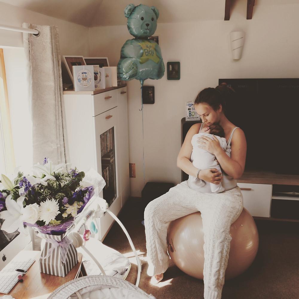 Best-aberdeen-family-children-photographer-montrose-arbroath-new-mother-cradling-newborn-baby-on-balance-ball