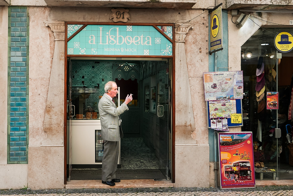 lisbon old man at a storefront window, a lisboeta cafe in Portugal