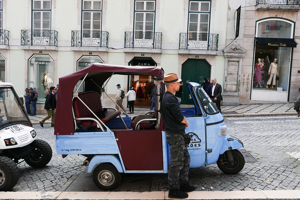 Lisbon, Portugal street photography, tuk tuk driver in a hat on a cobbled street