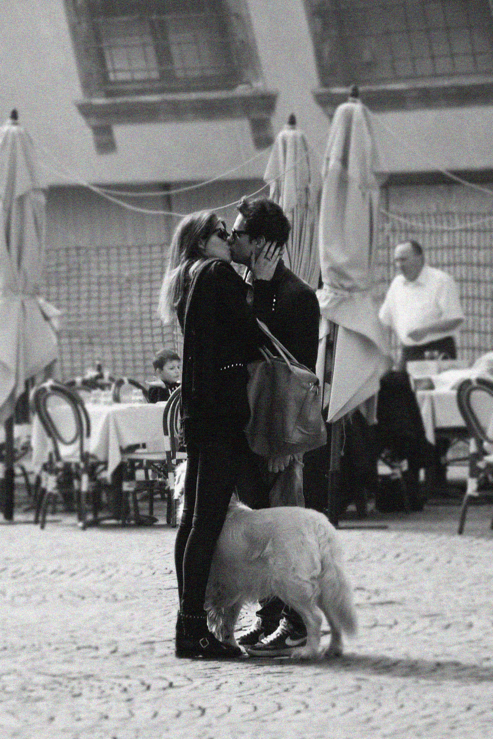 kissing couple in Italy in black and white, romantic embrace with a dog