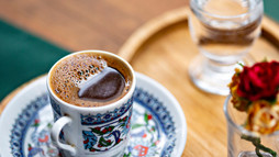 Traditional Turkish coffee. Turkish coffee in small cup served with glass of water and swe