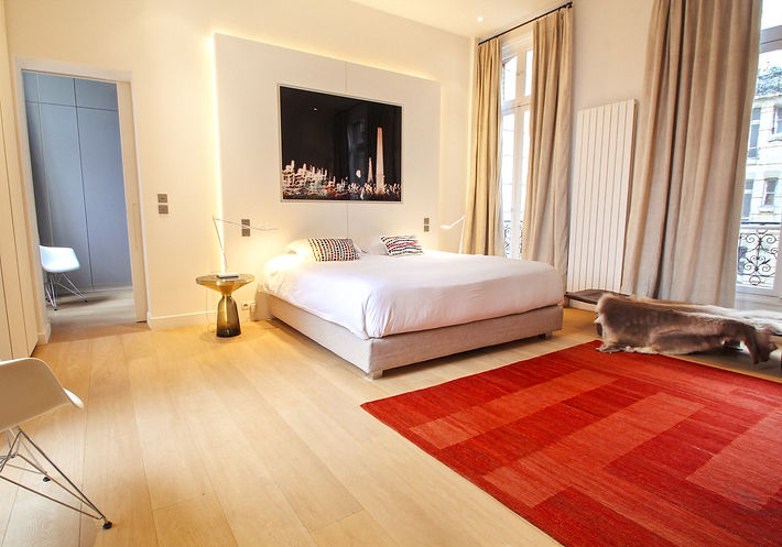 "The Master Bedroom, ""LA CONCORDE"" photograph on plexi, Treca Platinum king-size bed, Egyptian cotton linens by Eglantine Collection, cushions from Galeries Lafayette Maison, Sebastian Herkner Bell side tables, Charles Eames Tour Eiffel armchairs, burgundy red modern Turkish kilim, antique Nagaland wooden bed, Paris, Trocadero, Christi Rolland Home Interiors"