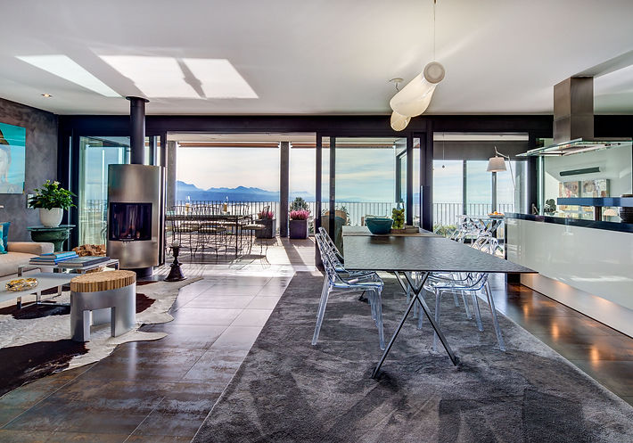 View from the Home Cinema and TV Room, Rimini carpet from Casajardinia Interiors, polycarbonate dining chairs Spider by Bontempi, Tailor Italian dining table with Ecomalta top, Empirico suspension lamp by Artemide, Lake Geneva, Christi Rolland Home Interiors