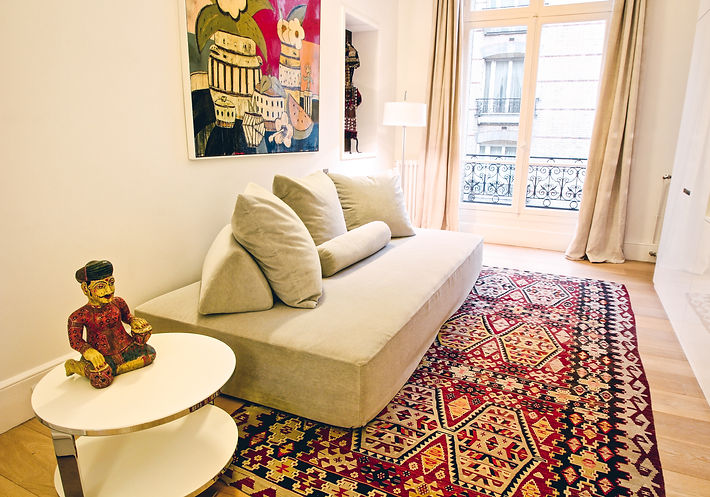 The Home Cinema Room, handwoven Turkish kilim, Sherazade canape by Edra in velvet light green tone, side table EILEEN, Rajasthani wooden statues, Rob Tucker's oil and resin on board, Turkmenistan traditional wedding outfit on display nook, Trocadero, Paris, Christi Rolland Home Interiors