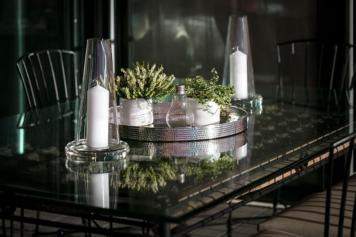 The Teak Terrace with a View, Wrought iron dining table with antique Rajasthani door as table base over glass top, composition of plants on metal hammered tray from Janam, Lake Geneva, Christi Rolland Home Interiors
