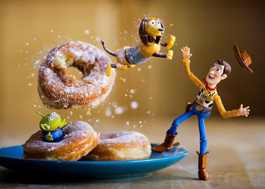 Toy Story Slinky Dog jumps through an airborne donut while Woody looks on