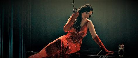 Carmen sitting sexy atop a piano