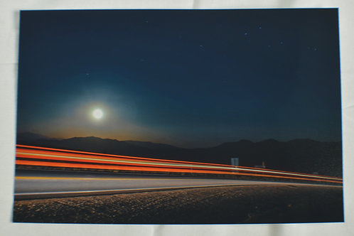 Cars passing by a full moon.