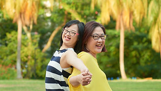 Photo shows a mother and daughter with down syndrome having a good time at the park.