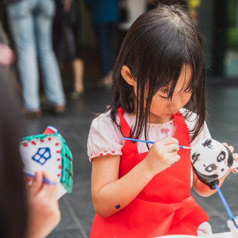 A little girl painting a panda