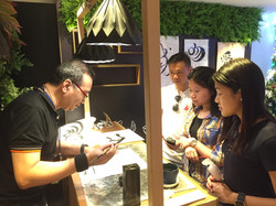 Photo of Wesley showcasing his calligraphy work to the participants