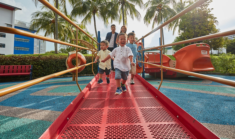 Photo shows a family of five having a good time at the playground.