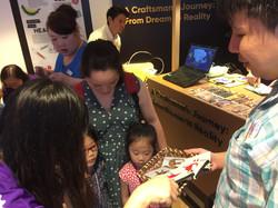 Photo of Zhiyu sharing his artworks with children.