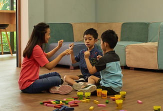 Photo shows an adult playing with two children with disabilities.