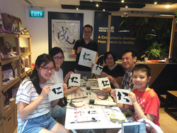 Photo of Wesley and his workshop participants holding up their calligraphy work.