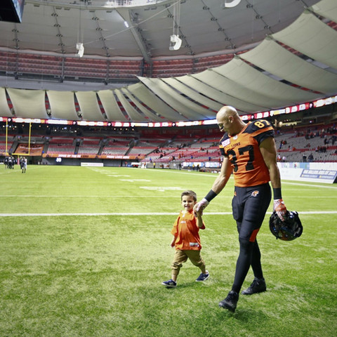 Marco Iannuzzi with son walking across BC Place stadium field
