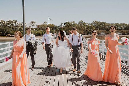 Bride and groom with bridal party walking down pier in Brisbane