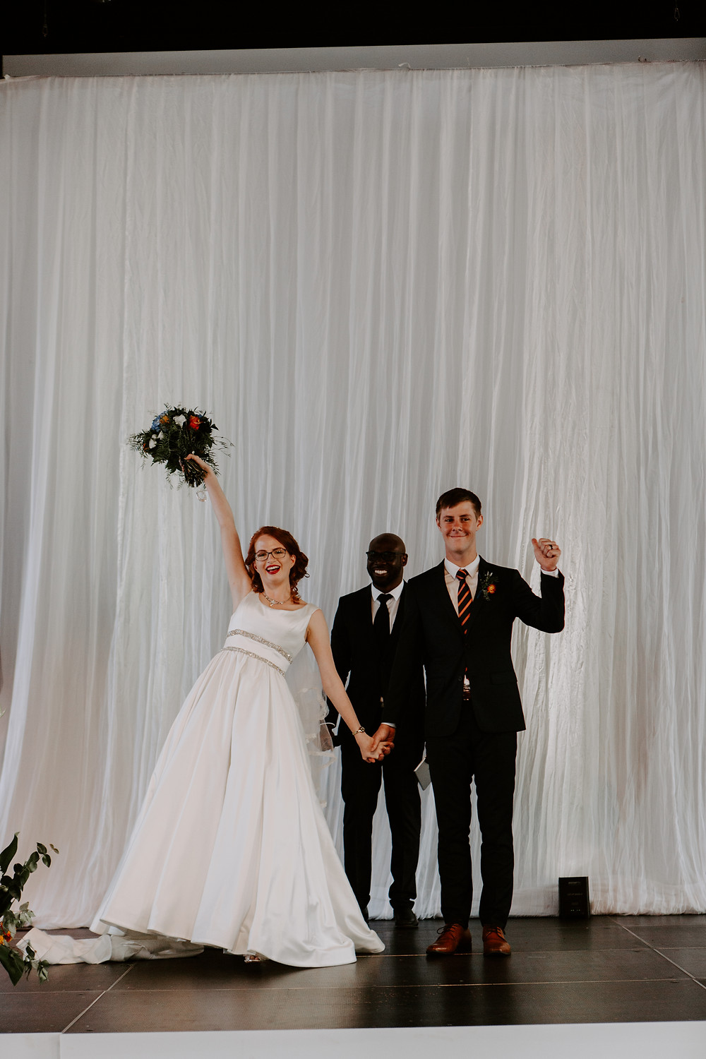 bride and groom cheer after ceremony celebrate wedding