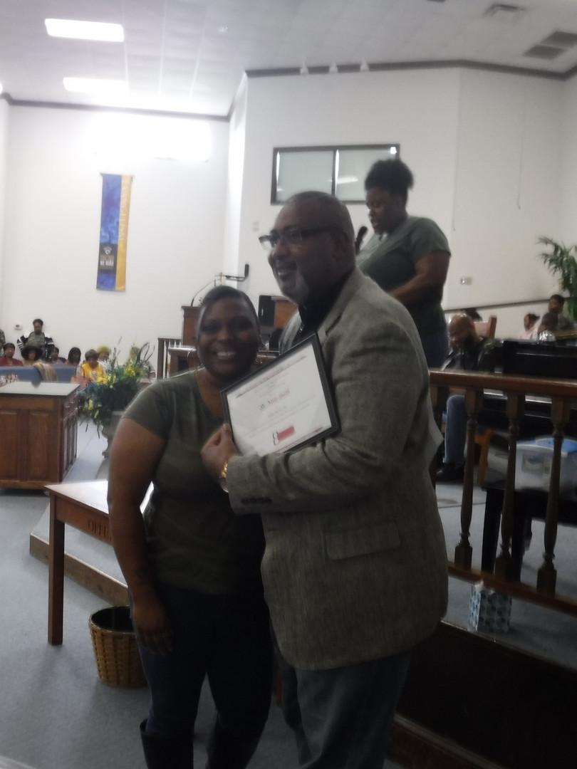 Bro. Tony Smith accepting certificate on behalf of Sis. Meta Smith