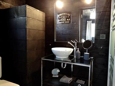 La salle de bain de la cabane en voliges noires.Le plan vasque est  en verre et métal. Douche et wc