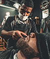 a-barber-grooming-a-man-s-beard-2881253.