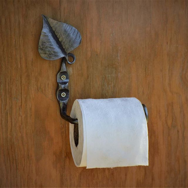 Toilet paper holder forged from a railro