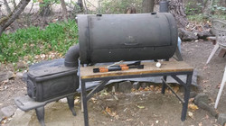 Smoker made from an old tank, woodstove, and other scrap odds and ends