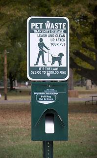 Sign at dog park encouraging proper pet