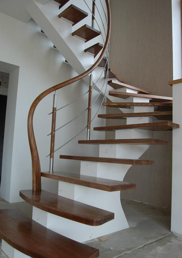 Stairs with white-painted steel construction and curved oak handrail.