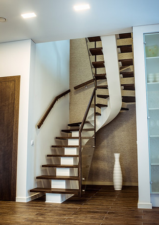 Stairs with white-painted steel construction and darkish steps from oak + glass railings and oak handrail.