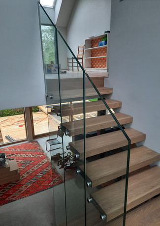 staircase with durable steps from oak and glass railings.