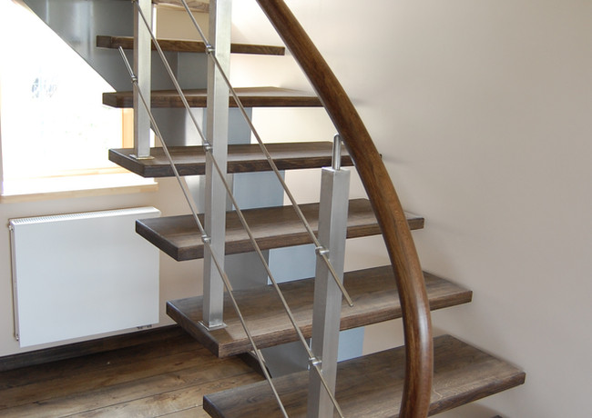 Stairs with steel construction and curved oak handrail.